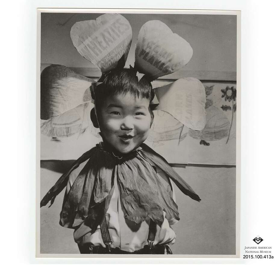 U.S. War Relocation Authority photo of Bob Kaneko of Berkeley as a child in the Topaz, Utah, internment camp. He is wearing a headress made out of cereal boxes. Photo: Japanese American National Museum / Japanese American National Museum