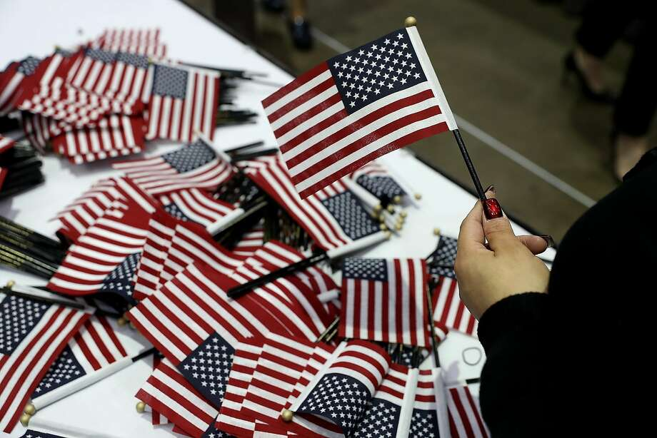 A worker passes out American flags during a naturalization ceremony Wednesday held by U.S. Citizenship and Immigration Services at the Los Angeles Convention Center. Photo: Justin Sullivan, Getty Images