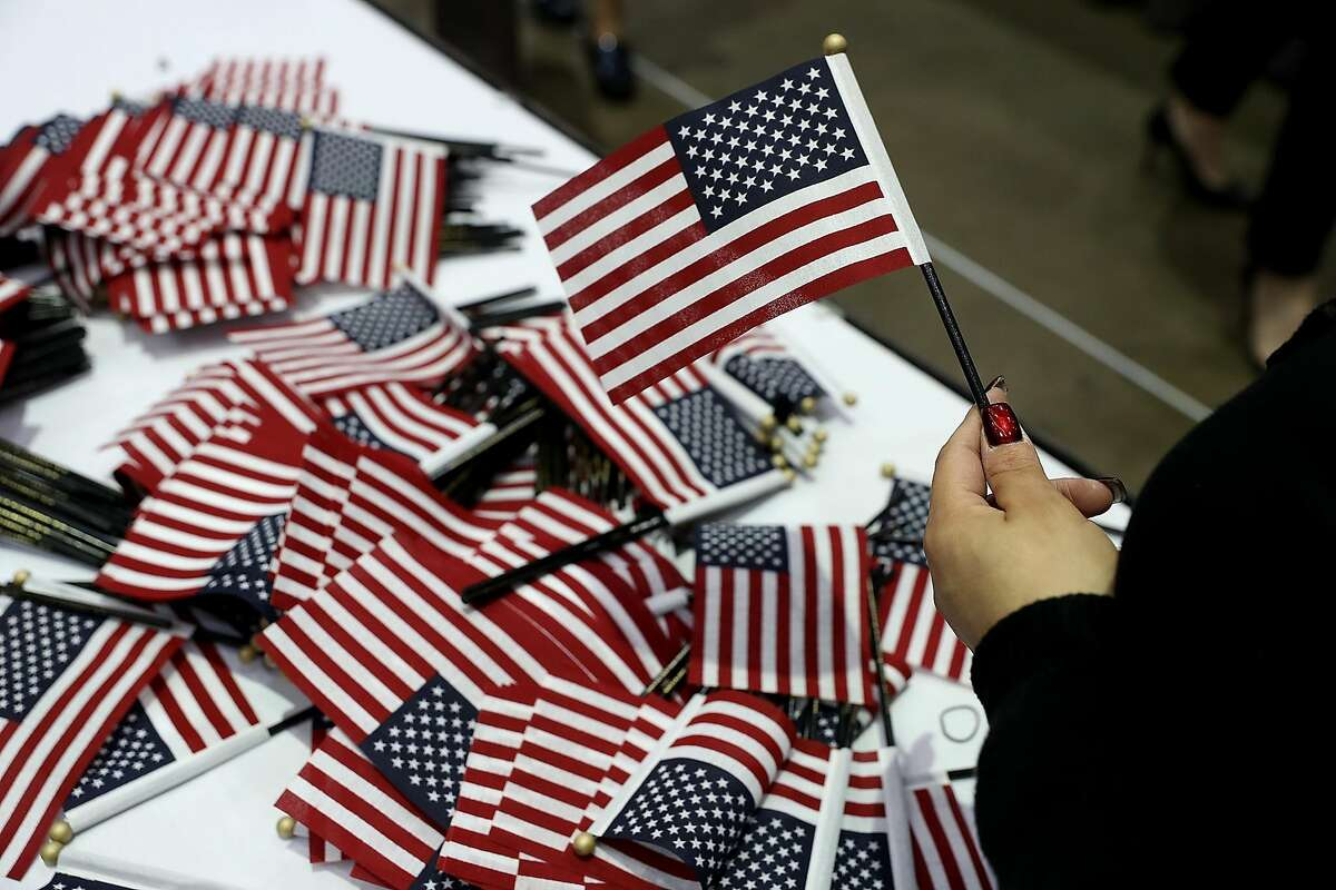 LOS ANGELES, CA - FEBRUARY 15: A workers passes out American flags during a naturalization ceremony held by U.S. Citizenship and Immigration Services at the Los Angeles Convention Center on February 15, 2017 in Los Angeles, California. 6,700 immigrants became U.S. citizens during two naturalization ceremonies held at the Los Angeles Convention Center. (Photo by Justin Sullivan/Getty Images)
