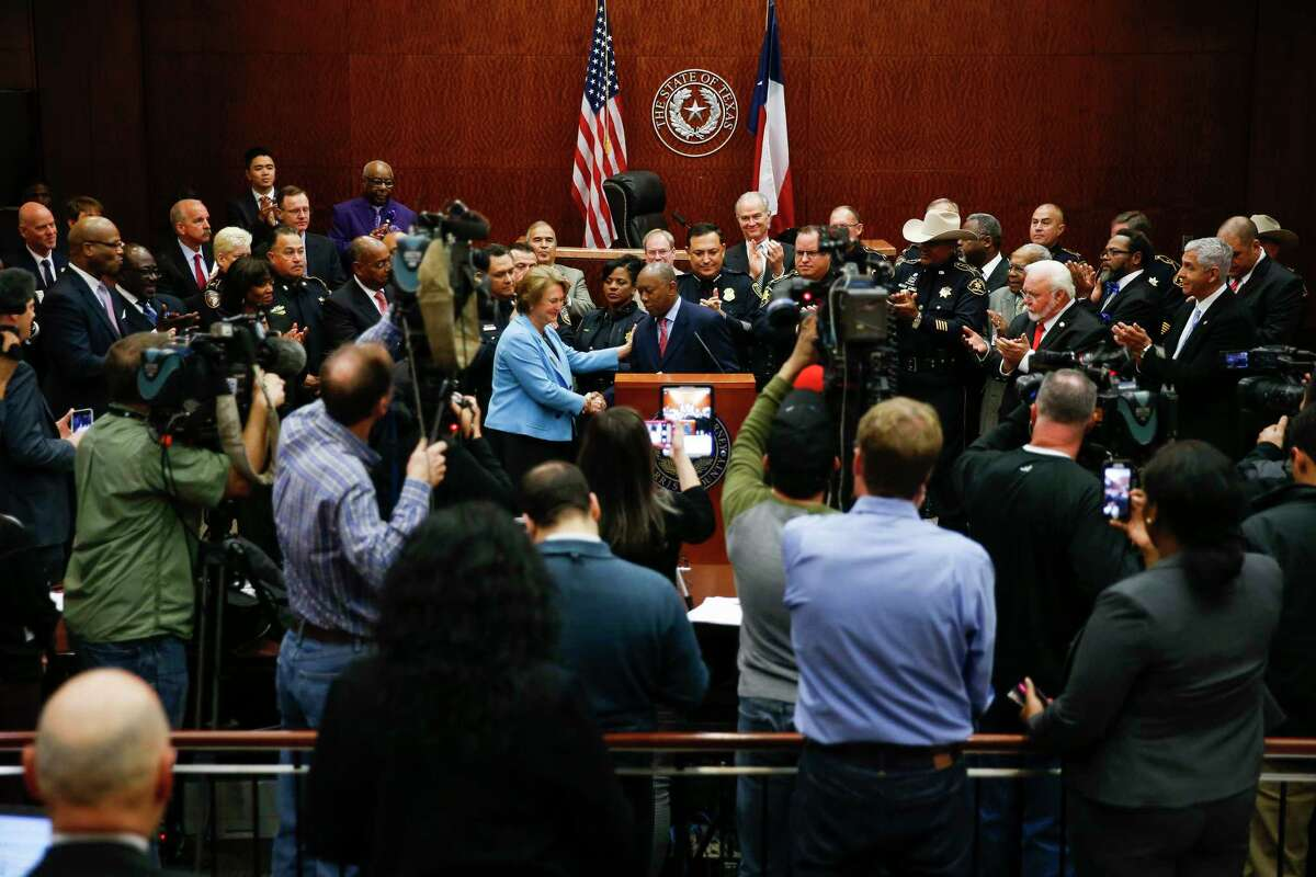 Harris County district attorney Kim Ogg, center left, introduces Houston mayor Sylvester Turner, center, after she announced a new policy to decriminalize low-level possession of marijuana Thursday, Feb. 16, 2017 in Houston. The new policy means that most misdemeanor offenders with less than four ounces of marijuana will not be arrested, ticketed or required to appear in court if they agree to take a four-hour drug education class.