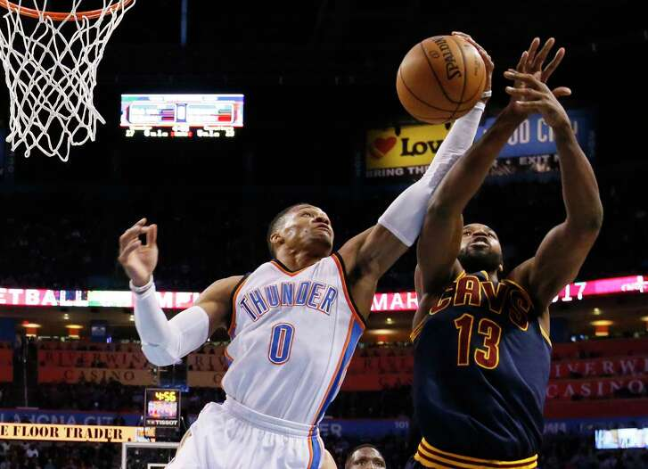 Oklahoma City Thunder guard Russell Westbrook (0) grabs a rebound in front of Cleveland Cavaliers center Tristan Thompson (13) in the first quarter of an NBA basketball game in Oklahoma City, Thursday, Feb. 9, 2017. (AP Photo/Sue Ogrocki)