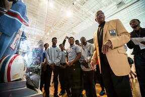 Hall of Famer Kenny Houston leads students from Pro-Vision Academy through a tour of the Pro Football Hall of Fame's Gridiron Glory, traveling exhibit on the campus of Texas Southern University on Thursday, Feb. 16, 2017, in Houston.