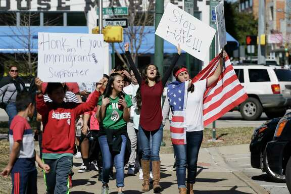 """Immigrant supporters marches with others during a protest outside the Grayson County courthouse in downtown Sherman, Texas, Thursday, Feb. 16, 2017. In an action called """"A Day Without Immigrants,"""" immigrants across the country are expected to stay home from school, work and close businesses to show how critical they are to the U.S. economy and way of life."""