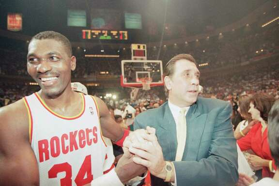 Houston Rockets center Hakeem Olajuwon, left, and Rockets coach Rudy Tomjanovich shake hands as they celebrate their second straight NBA championship, Wednesday, June 14, 1995, in Houston. The Rocket beat the Orlando Magic 113-101 in Game 4 of the NBA Finals to sweep the Magic 4-0. (AP Photo/Rick Bowmer)