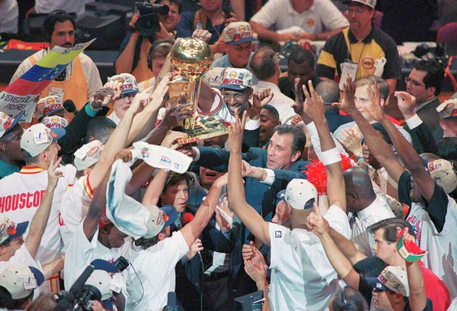 Houston Rockets coach Rudy Tomjanovich, center, is surrounded by his team as they hoist the NBA Championship Trophy overhead following the Rockets 113-101 victory over the Orlando Magic in Game 4 of the NBA Finals, Wednesday, June 14, 1995, in Houston. The win gave the Rockets their second straight NBA title, with a 4-0 sweep in the best-of-seven series. (AP Photo/Pat Sullivan) Photo: Pat Sullivan / Associated Press / AP