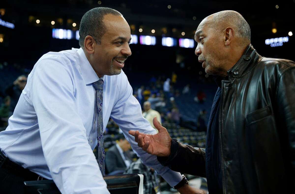Baseball Hall of Famer Reggie Jackson talks with Charlotte Hornets' announcer Dell Curry, father of Golden State Warriors' Stephen Curry, at Oracle Arena in Oakland, Calif., on Monday, January 4, 2016.