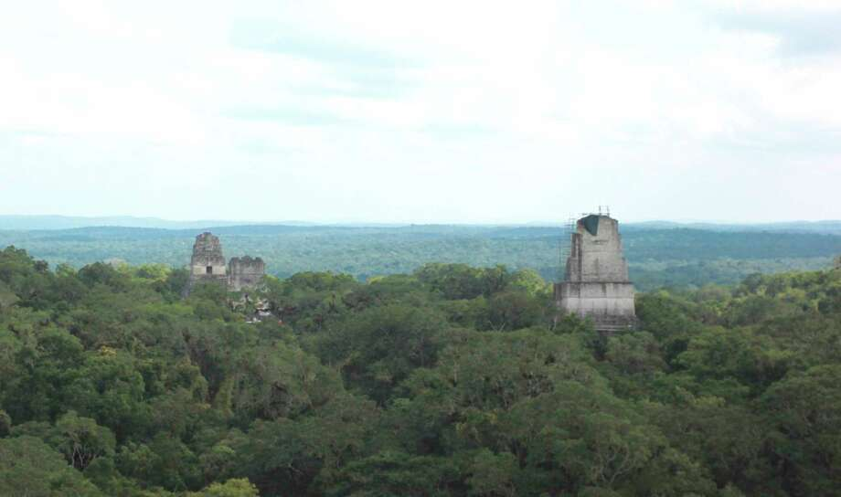 In this photograph taken Dec. 6, 2016, three of Tikal National Park's temples rise above the tree line as viewed from the top of another temple, Temple IV. The sprawling park in northern Guatemala is one of the country's top travel attractions, showcasing the Mayan civilization's engineering feats. (AP Photo/Manuel Valdes) ORG XMIT: NYLS207 Photo: MANUEL VALDES / MANUEL VALDES