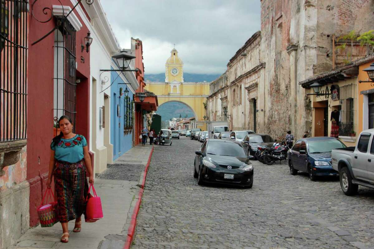 In this photograph taken Dec. 14, 2016, an indigenous woman walks on the street where the Santa Catalina arch is located in Antigua Guatemala, Guatemala. Established in 1543 as the territorial capital of the Spanish crown and abandoned after a series of earthquakes, the colonial city is home to preserved and colorful churches and mansions from the era and now is a tourist center.(AP Photo/Manuel Valdes) ORG XMIT: NYLS205