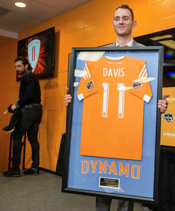 Former Houston Dymano midfielder Brad Davis holds up a framed Dynamo jersey after signing a one-day contract to retire with the team during a news conference at BBVA Compass Stadium on Thursday, Feb. 16, 2017, in Houston. Davis played for the Dymano from 2006Ð2015, scoring 41 goals in 271 appearances with the MLS team.