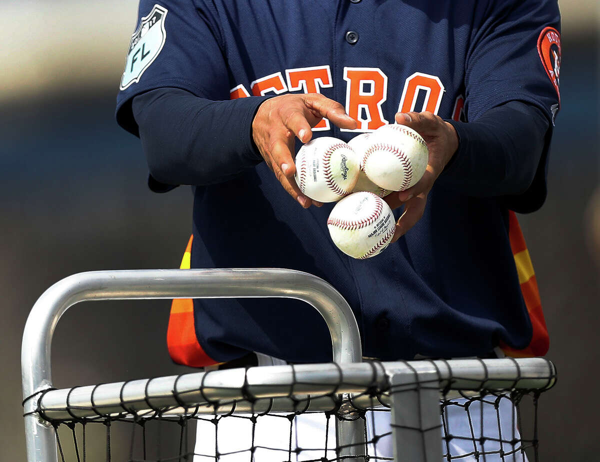 Houston Astros bullpen catcher Javier Bracamonte throws baseballs into a basket during spring training at The Ballpark of the Palm Beaches, in West Palm Beach, Florida, Thursday, February 16, 2017.