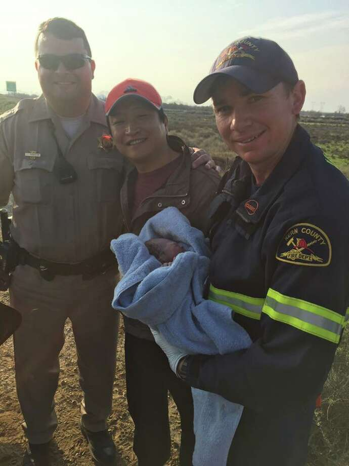 Buttonwillow CHP officers Jason Kremsdorf and Manny Garcia and new father Phillip Lee pose with the baby boy they delivered on the side of the highway on Feb. 14, 2017.  Photo: Photo: Adam Taylor/Buttonwillow CHP