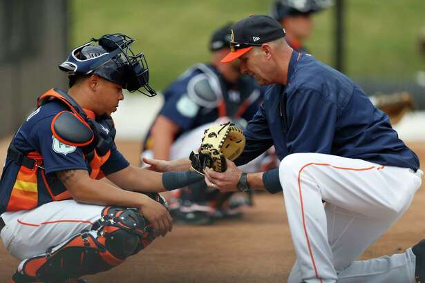Houston Astros catching coordinator Mark Bailey adjusts Houston Astros catcher Juan Centeno's glove during spring training at The Ballpark of the Palm Beaches, in West Palm Beach, Florida, Thursday, February 16, 2017.