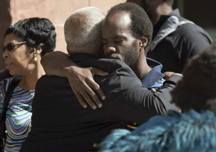 Kalion Busby, right, brother of Qwalion Busby, hugs his father, Ernest Busby, after the punishment phase of the trial Feb. 16 of Qwalion Busby and Marquita Johnson, who were convicted of injury to a child by omission in regard to the death of their infant son in 2015. Photo: Darren Abate /For The San Antonio Express-News