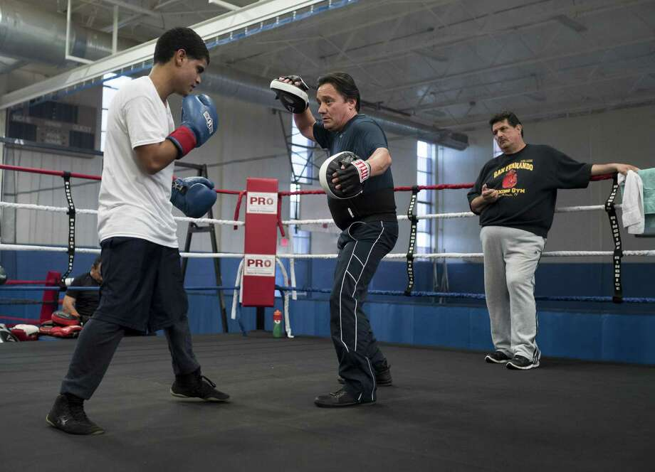 Jesse Cantu, center, works out with Carlos Tejeda, left, and Orlando Mendiola at Lincoln Community Center, Tuesday, Feb. 14, 2017, in San Antonio. Photo: Darren Abate /For The Express-News / Darren Abate Media