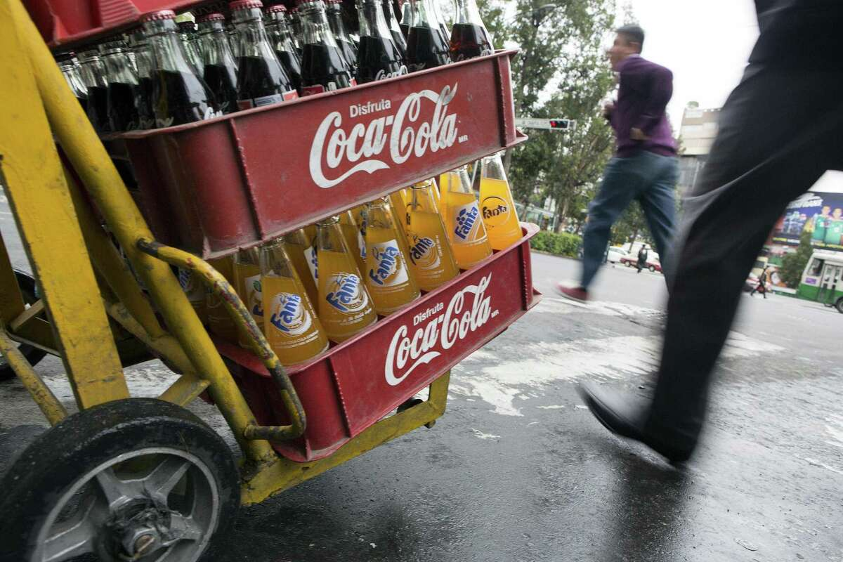 A worker pushes a hand truck with Coca-Cola products while making deliveries in Mexico City. Coca-Cola bottled in Mexico, dubbed