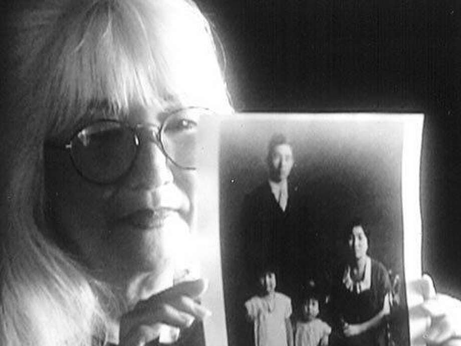 """Emiko Omori holds a family picture in her film """"Rabbit in the Moon."""" Photo: CAAMFest"""