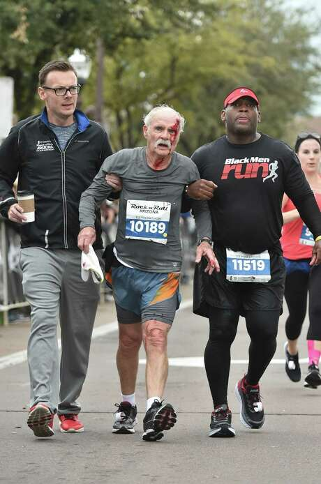 Colin Jackson (left) and San Antonio's Nathanael Dillard (right) help injured runner John Wilkie during the Rock 'n' Roll Marathon in Phoenix on Jan. 15 2017. Photo: Courtesy Photo