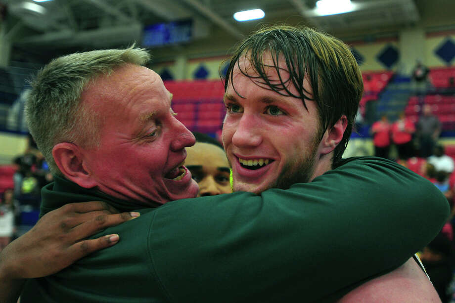 East Chambers head coach Todd Sutherland hugs Dylan Silcox after the team won the boys' basketball Class 3A regional finals in Waco on Saturday afternoon. Silcox scored the winning basket with 3.4 seconds on the clock.  Photo taken Saturday 3/5/16 Ryan Pelham/The Enterprise Photo: Ryan Pelham / ©2016 The Beaumont Enterprise/Ryan Pelham