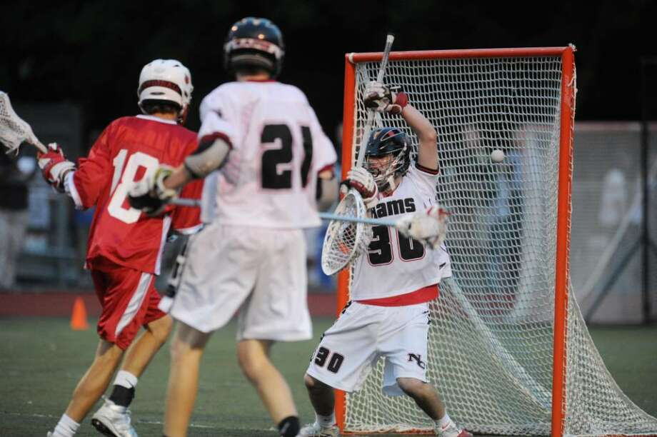 New Canaan golaie Thomas Carey, right, can not stop a 2nd quarter goal by Greenwich High School's Pete Cabrera (not in photo), during 2nd quarter action of the FCIAC Lacrosse Championship at Brien McMahon High School, Norwalk, Friday, May, 28, 2010.  At left is Eric Foote of GHS, #18, looking on.  The score at the half is 5-1 GHS over NC. Photo: Bob Luckey / Greenwich Time