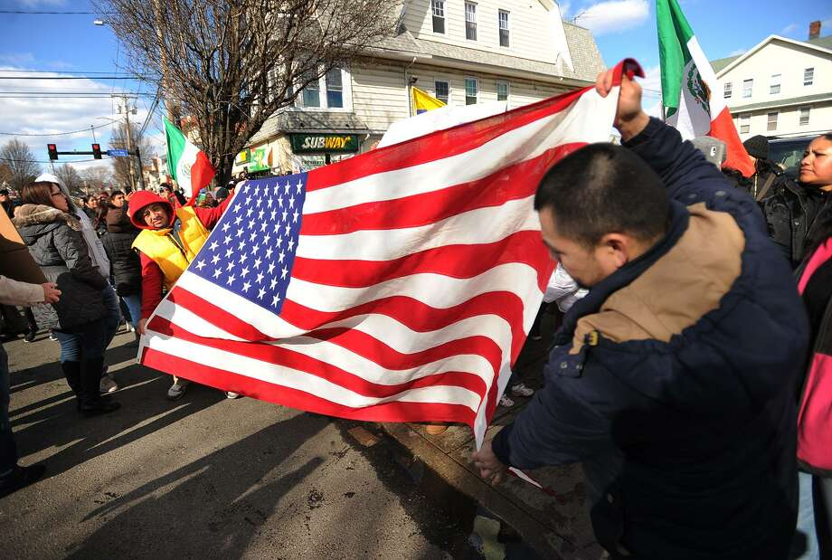"Jose Martinez, left, and Miguel Ramirez, both of Bridgeport, unfurl a large American flag during the ""A Day Without Immigrants"" march and rally on Madison Avenue in Bridgeport, Conn. on Thursday, February 16, 2017. About five hundred people participated in the event. Photo: Brian A. Pounds / Hearst Connecticut Media / Connecticut Post"