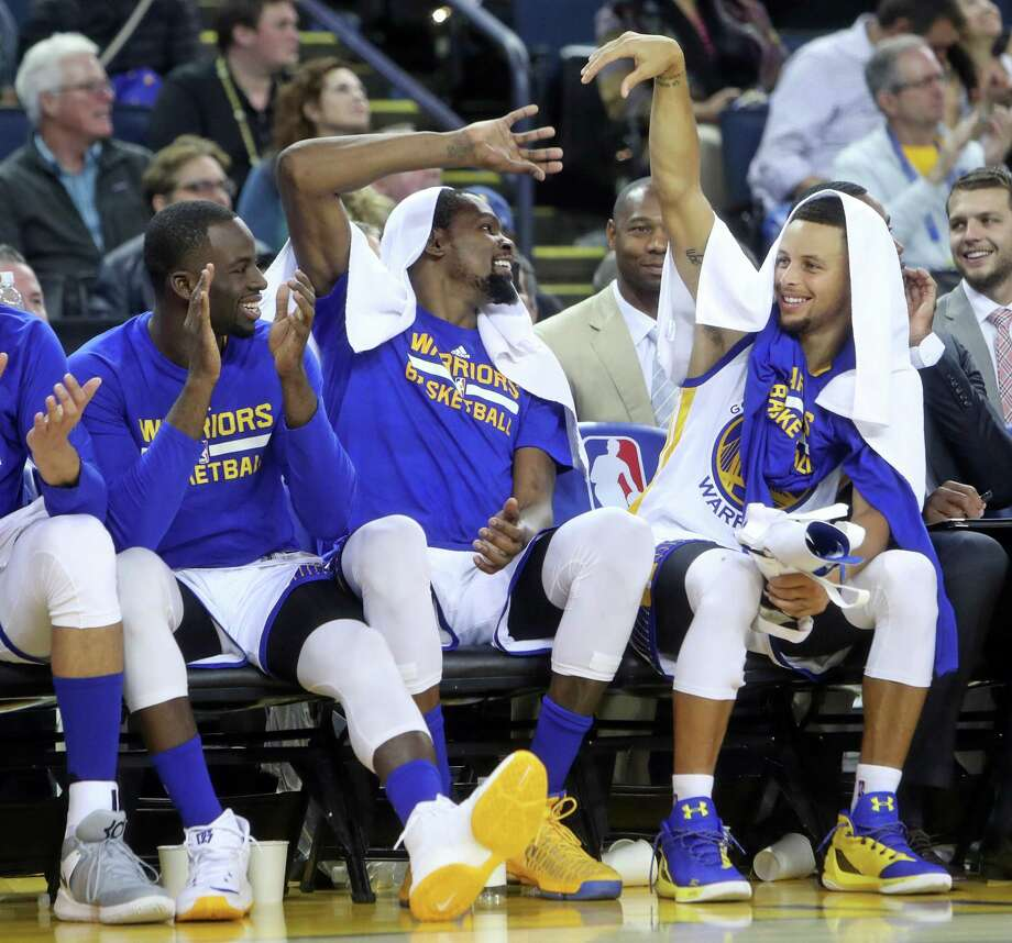Golden State Warriors' Draymond Green, Kevin Durant and Stephen Curry enjoy final minutes of 122-96 win over Oklahoma City Thunder in NBA game at Oracle Arena in Oakland, Calif., on Thursday, November 3, 2016. Photo: Scott Strazzante / The Chronicle / **MANDATORY CREDIT FOR PHOTOG AND SF CHRONICLE/NO SALES/MAGS OUT/TV