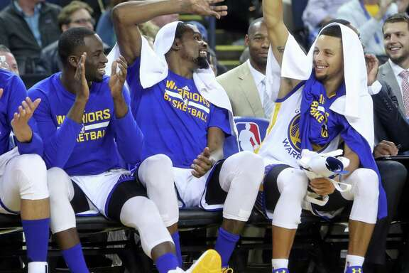 Golden State Warriors' Draymond Green, Kevin Durant and Stephen Curry enjoy final minutes of 122-96 win over Oklahoma City Thunder in NBA game at Oracle Arena in Oakland, Calif., on Thursday, November 3, 2016.