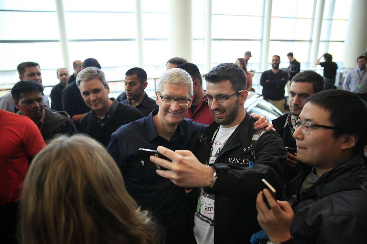 Apple chief executive officer Tim Cook (center left) poses for photos with WWDC attendees after speaking during the keynote for the Apple Worldwide Developers Conference 2014 at Moscone West in San Francisco, Calif.
