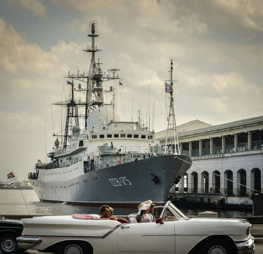 Tourists in a old American car pass by Russian Vishnya (also known as Meridian) class warship CCB-175 Viktor Leonov, docked, on February 26, 2014, at Havana harbor. The Vishnya class ships are used for gathering intelligence. They ships were built in the 1980s for the Soviet Navy and are still deployed within the Russian fleet. Photo: ADALBERTO ROQUE /AFP /Getty Images / ONLINE_YES