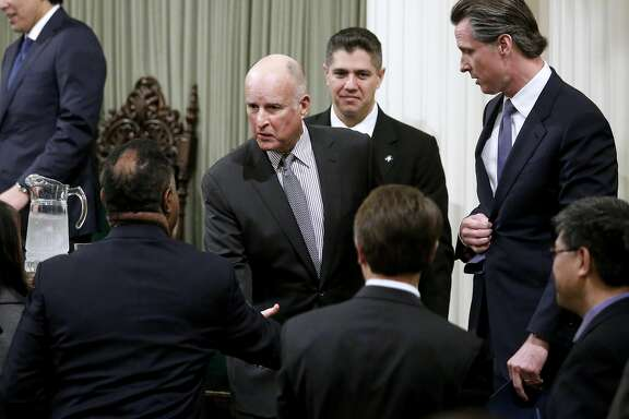 California Gov. Jerry Brown, middle, with Lt. Gov. Gavin Newsom, far right, after delivering his State of the State speech in the State Assembly Chambers at the State Capitol building in Sacramento, Calif., on Tuesday, Jan. 24, 2017. (Gary Coronado/Los Angeles Times/TNS)