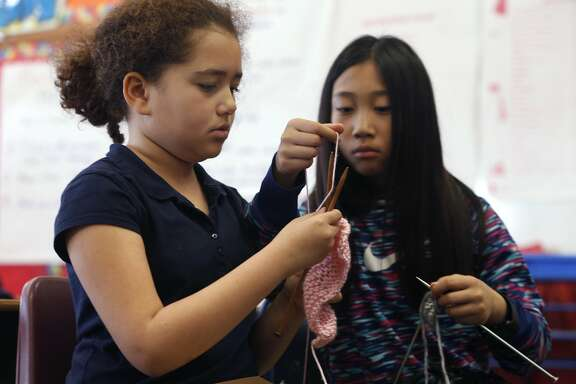 Esperanza Quiles (left) and Adreanna Chum make scarves for the homeless in a knitting club at John Muir Elementary School in San Francisco, Calif. on Thursday, Feb. 16, 2017.