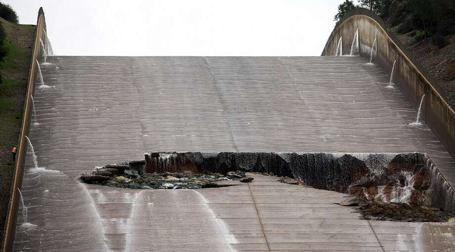 Department of Water Resources personnel, left, inspects a hole was torn in the spillway of the Oroville Dam while releasing approximately 60,000 cubic-feet-second of water in advance of more rain on February 7, 2017 in Oroville, California. Photo: Max Whittaker/Prime, Special To The Chronicle