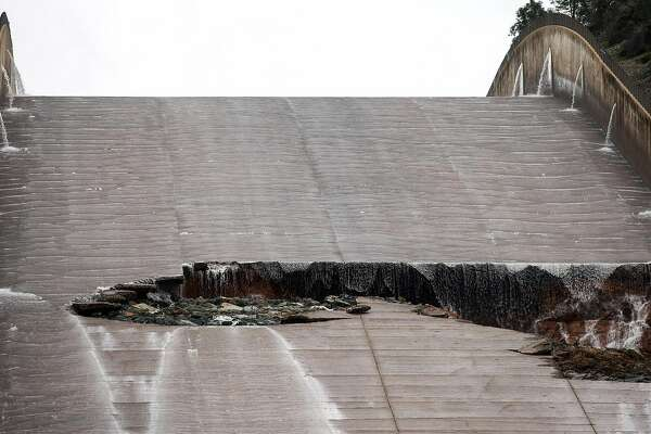 Department of Water Resources personnel, left, inspects a hole was torn in the spillway of the Oroville Dam while releasing approximately 60,000 cubic-feet-second of water in advance of more rain on February 7, 2017 in Oroville, California.
