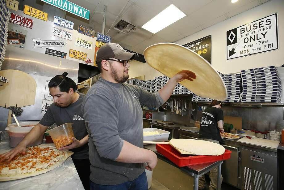 Jonathon Rangel tosses some pizza dough at A Slice of New York in San Jose as Miguel Rubio puts the topping on the pizza. The pizzeria is in the process of transitioning from a traditional ownership structure to a cooperative. Photo: Tony Avelar, Special To The Chronicle