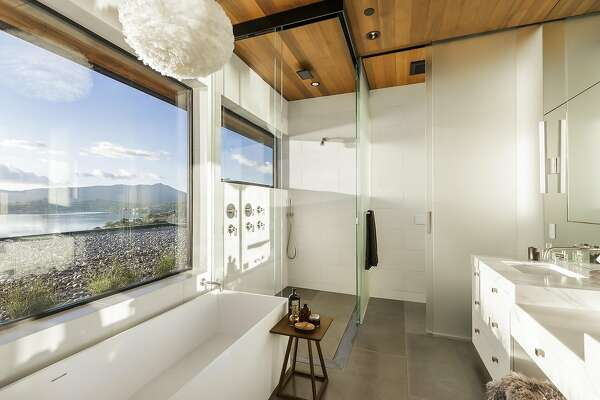 The master bathroom's walk-in shower features multiple body sprayers and a rain head.