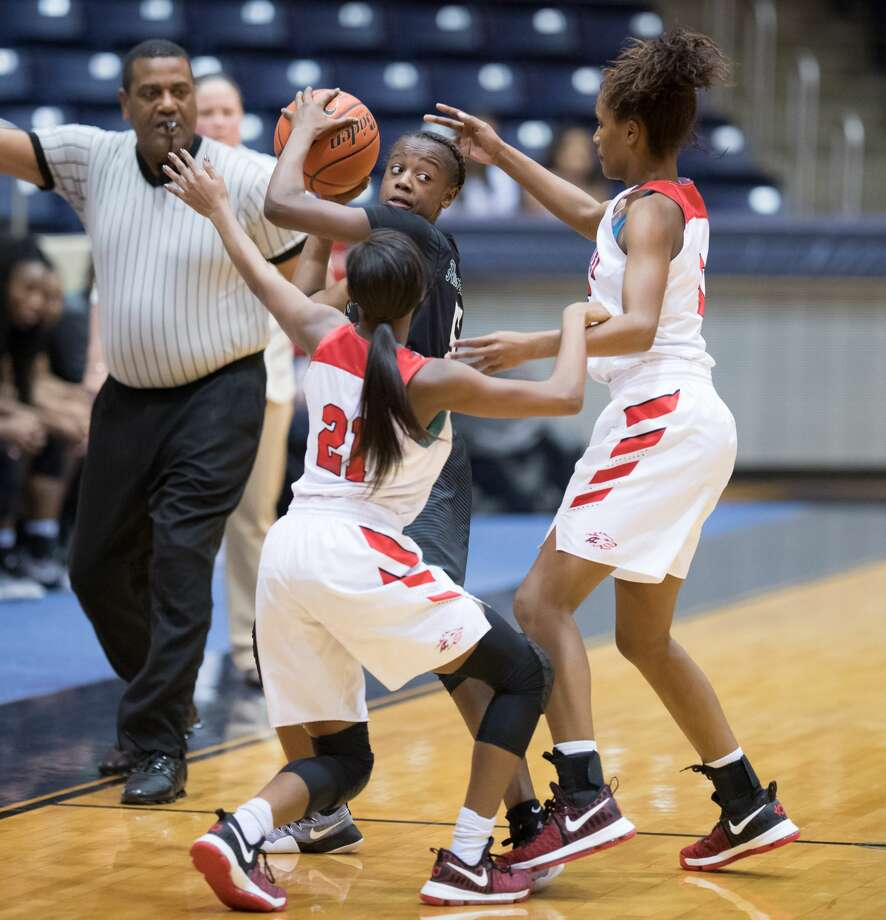 Taelor Purvis (5) of the Hightower Hurricanes attempts to pass the ball with Dyani Robinson (21) and Dezeree White (5) both of the Langham Creek Lobos defending in 6A Girls Basketball Area Playoffs on Thursday, February 16, 2017 at the Coleman Coliseum in Houston, Texas. Photo: Wilf Thorne/For The Chronicle