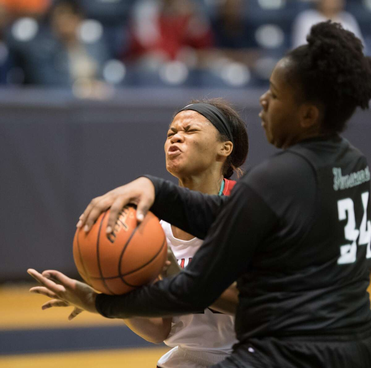 Rashonda Schaeffer (13) of the Langham Creek Lobos grimaces as she runs into Winnie Kuimi (34) of the Hightower Hurricanes in 6A Girls Basketball Area Playoffs on Thursday, February 16, 2017 at the Coleman Coliseum in Houston, Texas.