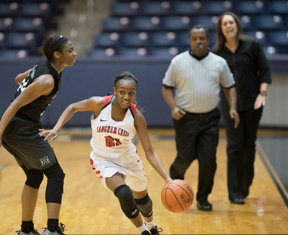 Dyani Robinson (21) of the Langham Creek Lobos dribbles around a Hightower Hurricanes player in 6A Girls Basketball Area Playoffs on Thursday, February 16, 2017 at the Coleman Coliseum in Houston, Texas.
