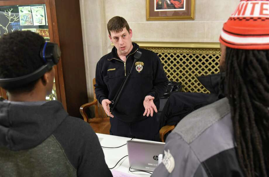 Lt. Brian Wolfgang, center, answers questions from Sheldon Allen of Albany, left, and Corey Gittens of Albany as the Albany Fire Department holds an open house at Albany City Hall on Thursday, Feb. 16, 2017 in Albany, N.Y. The event was to provide information for those interested in becoming a city firefighter. (Lori Van Buren / Times Union) Photo: Lori Van Buren / 20039714A
