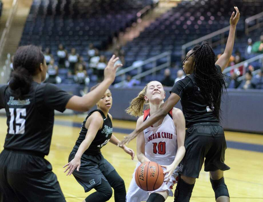 Briley Perkins, center, who led Langham Creek with 19 points, is fouled by Hightower's Lenecia Mitchell, right, as she drives to the basket during Thursday night's Class 6A Region III area-round playoff game. Photo: Wilf Thorne / © 2017 Houston Chronicle