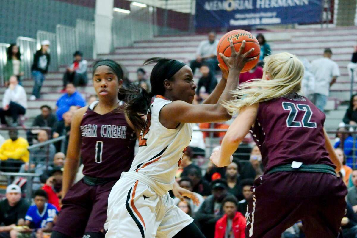 Dobie's Victoria Onozie(32) drives to the basket past Clear Creek's Hannah Froeschl (22 Thursday, Feb. 15 at Pearland High School.