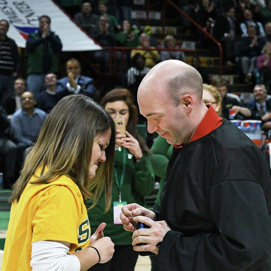 Erin Tobin, left, of Rensselaer is offered an engagement ring by Steve Duckett of Queensbury during a time out in Thursday's Siena game at the Times Union Center Feb. 16, 2017 in Albany, NY. She accepted his proposal.  (John Carl D'Annibale / Times Union) Photo: John Carl D'Annibale / 20039396A