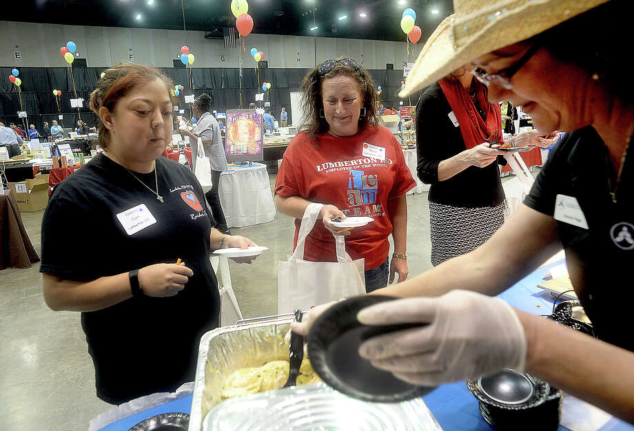 Vanessa Clark (left) and Lynelle Taylor with Lumberton ISD food services await a sample of cheese ravioli from Waypoint's Natalie Page at the 17th annual Region V Food Service Co-op Food Show Thursday at the Beaumont Civic Center. Lunch ladies and administrators from school districts throughout the area made their way through the rows of booths offering samples of food and products from a variety of businesses that service school cafeterias. Photo taken Thursday, February 16, 2017 Kim Brent/The Enterprise Photo: Kim Brent