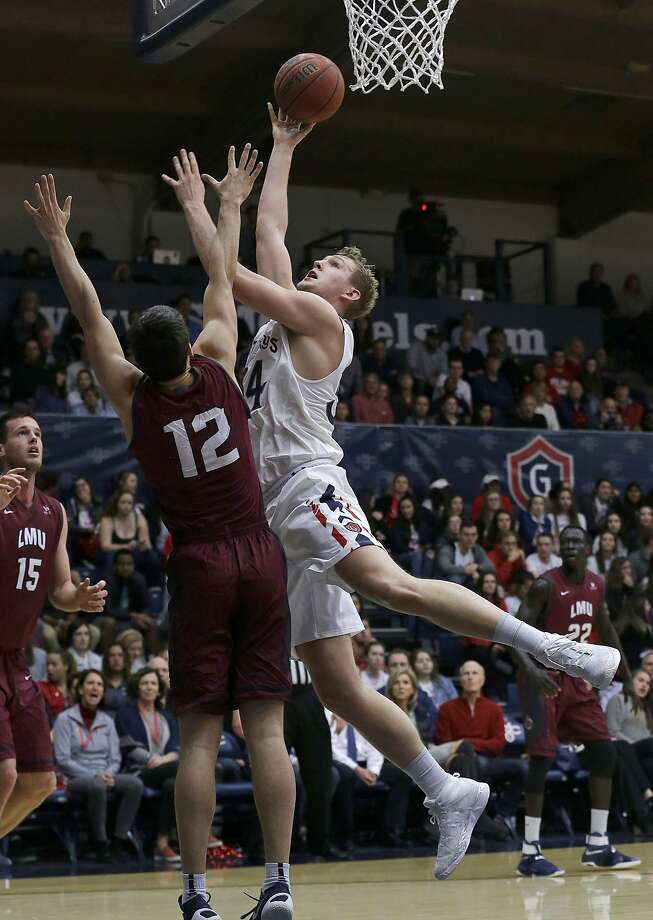The Gaels' Jock Landale (right) shoots against Loyola's Steven Haney (12) during the first half when Landale scored 16 points. Photo: Jeff Chiu, Associated Press