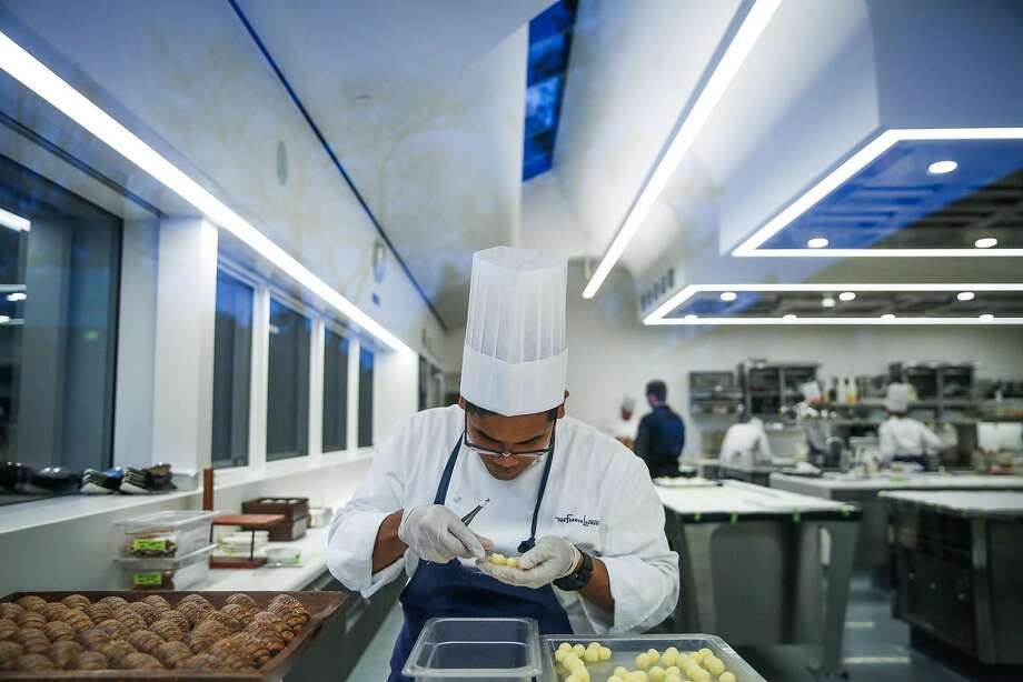 Jonas Corpuz sorts butter while prepping food in the French Laundry's new kitchen, which includes new windows and a new ceiling designed to look like flowing tablecloths. Photo: Gabrielle Lurie, The Chronicle