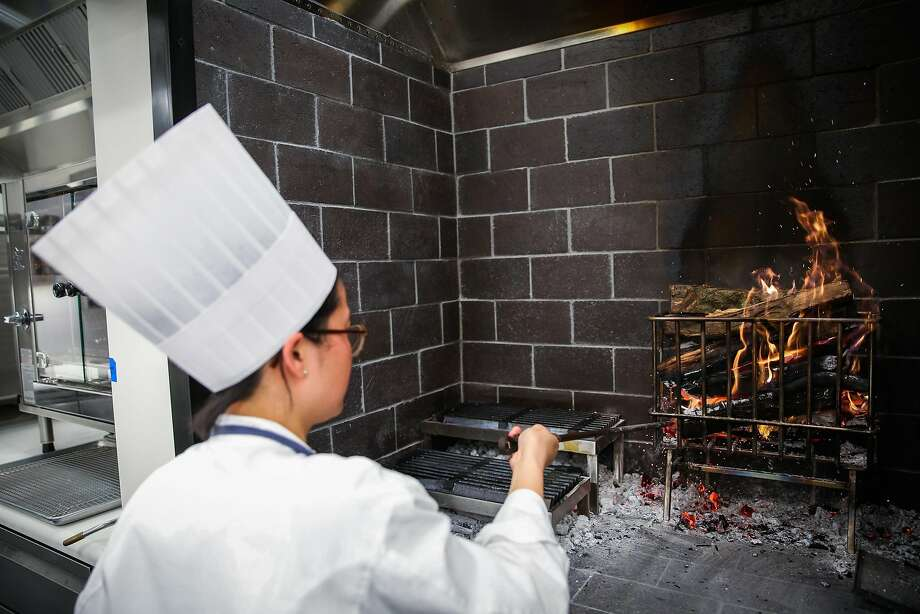 Christine Ng works the wood fire in in the new kitchen of the French Laundry. Photo: Gabrielle Lurie, The Chronicle