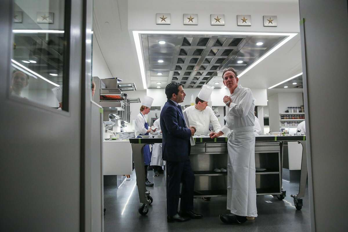 (l-r) Manager Michael Minnillo speaks with chef Thomas Keller in the kitchen at The French Laundry restaurant in Yountville, California, on Thursday, Feb. 16, 2017.