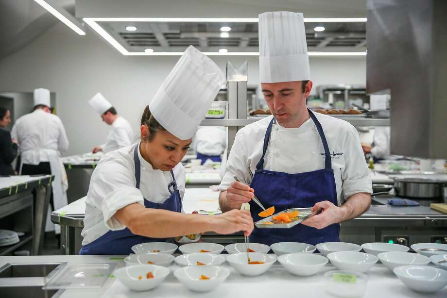 Catherine Takayama (left) and executive pastry chef Elwyn Boyles add garnishes to a desert in the kitchen at The French Laundry restaurant in Yountville, California, on Thursday, Feb. 16, 2017. Photo: Gabrielle Lurie, The Chronicle