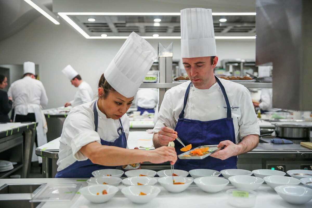 Catherine Takayama (left) and executive pastry chef Elwyn Boyles add garnishes to a desert in the kitchen at The French Laundry restaurant in Yountville, California, on Thursday, Feb. 16, 2017.