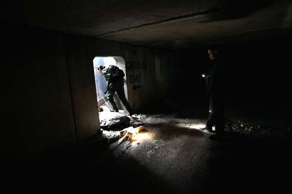 Border Patrol agent Colleen Agle (L) searches for evidence of drug smugglers in a drainage tunnel that runs under the U.S.- Mexico border on December 7, 2010 in Nogales, Arizona.