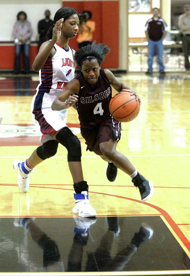 Silsbee's Ashlyn Martin drives past Hardin-Jefferson's Delberta Guillory-Smith during their area round 4A play-offs match-up in Kountze Thursday. Photo taken Thursday, February 16, 2017 Kim Brent/The Enterprise Photo: Kim Brent